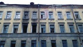 Un vieux bâtiment abandonné et des traces du feu - couvrez de suie sur les murs près des fenêtres Image libre de droits