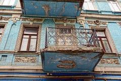 Un vieux balcon avec des fenêtres sur un mur de briques bleu Photo libre de droits