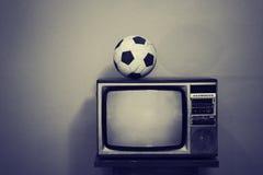 Un vieux ballon de football à une rétro TV, noire et blanche Images stock