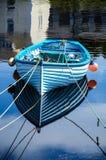 Un vieux bateau bleu avec les flotteurs de pêche oranges colorés reflétés dans l'eau bleue calme dans un port photos libres de droits