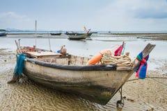 Un vieux bateau de pêche amarré a échoué sur la plage à marée basse Images stock