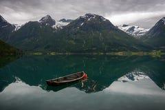 Un vieux bateau et quelques montagnes Image libre de droits