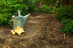Un vieux bidon et les gants d'arrosage se reposent photo libre de droits
