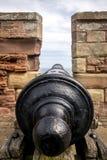 Un vieux canon se dirigeant par une tourelle sur une tour photos stock