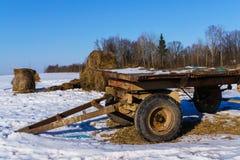 Un vieux chariot et les restes des petits pains de foin sur un champ en hiver photo stock