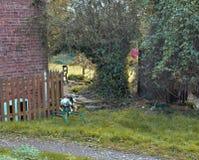 Un vieux cheval de basculage rustique en métal est dans un jardin vert Photo stock