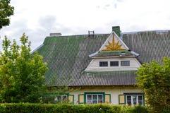 Un vieux cottage européen en bois rustique de maison fait de conseils avec des fenêtres avec des volets avec un toit triangulaire Photos libres de droits