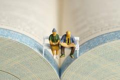 Un vieux couple lit un journal et un livre Photographie stock libre de droits