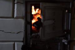 Un vieux fourneau carrelé Flamme dans le four photo libre de droits