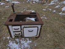 Un vieux fourneau en bois dans l'ouvert sur un pré images stock
