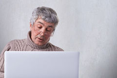 Un vieux grand-père en verres faisant un appel visuel par son ordinateur portable communiquant avec ses enfants Un retraité seul  Images libres de droits