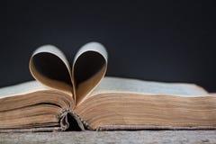 Un vieux livre avec les pages en forme de coeur Images libres de droits