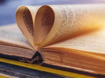 Un vieux livre ouvert avec des feuilles sous forme de coeur Photographie stock libre de droits