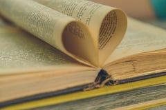 Un vieux livre ouvert avec des feuilles sous forme de coeur Photo stock