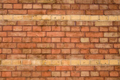 Un vieux mur de briques rouge avec deux lignes dans l'ocre Image stock