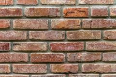 Un vieux mur des briques reconstituées avec une couleur rouge fortement fanée et des joints inégaux images stock