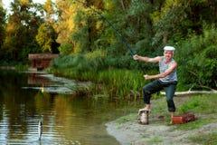 Un vieux pêcheur a pêché un poisson dans le lac Photographie stock