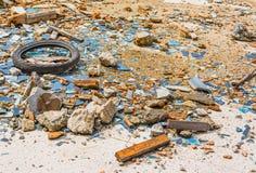 Un vieux pneu dans une zone en verre cassée Images stock