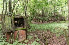 Un vieux puits abandonné et une maison de rapport Photos stock