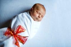 Un vieux sommeil nouveau-né de bébé de semaine enveloppé dans la couverture blanche avec l'arc rouge Image libre de droits
