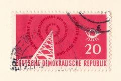 Un vieux timbre Allemand de l'Est rouge avec une image d'un émetteur radioélectrique Photos libres de droits