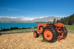 Un vieux tracteur rouge sur le rivage du lac Tekapo, Nouvelle-Zélande Image libre de droits