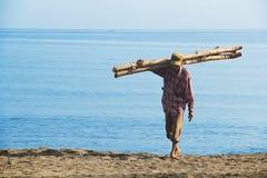 Un vieux villageois avec le bois de chauffage Images stock