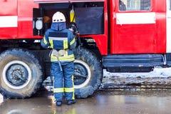 Un vigile del fuoco che sta vicino ad un'autopompa antincendio rossa e che tiene un ossigeno fotografie stock