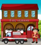 Un vigile del fuoco con un camion dei vigili del fuoco in una caserma dei pompieri Fotografia Stock