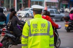 Un vigile urbano cinese aiuta il traffico diretto ad un intet occupato Fotografia Stock