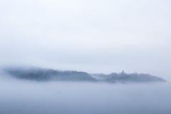 Un village émerge d'une mer des nuages Photographie stock