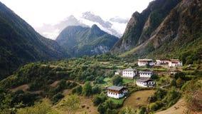 Un village tranquille sous la montagne de neige Photographie stock