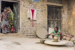 Un villageois produit des pots d'argile tandis que sa famille regarde dessus Photo stock