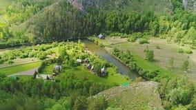 Un villaggio calmo al piede delle montagne vicino ad un piccolo fiume della montagna stock footage