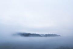 Un villaggio emerge da un mare delle nuvole Immagine Stock
