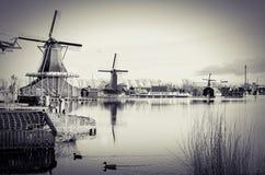 Un villaggio olandese del mulino a vento da un fiume Fotografie Stock Libere da Diritti
