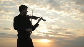 Un violinista joven en una camisa negra, jugando en el tejado almacen de metraje de vídeo