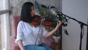 Un violinista que se sienta en una silla que toca un violín cerca de una ventana en un cuarto, tiro constante de la leva, cámara  almacen de video