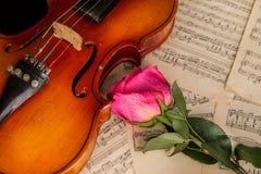 Un violon, une rose de rouge et une musique de feuille Image libre de droits