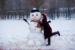 Un visage drôle de bonhomme de neige de petit baiser gai de fille Photographie stock