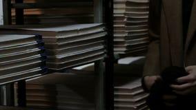 Un visiteur de bibliothèque dans des vêtements bruns marche entre les étagères avec des documents ?tag?res avec la vieille litt?r clips vidéos