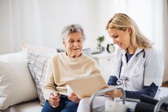 Un visiteur de santé et une femme supérieure s'asseyant sur un lit à la maison, parlant image stock