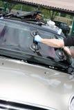 Un vitrier réparant et fixant la voiture cassée de pare-brise dans la rue de client ou le lieu de travail images libres de droits