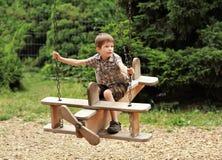 Un vol de garçon sur une oscillation plate en bois en parc Photographie stock libre de droits