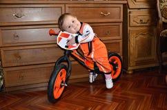 Un volante del abarcamiento del niño se sienta en una bici de la balanza Imágenes de archivo libres de regalías