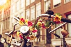 Un volante di vecchia bicicletta decorato con i fiori artificiali Via di Amsterdam Fotografia Stock Libera da Diritti