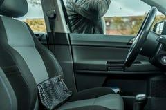 Un voleur de voiture essaye de frapper la fenêtre latérale sur une voiture avec son bras images stock