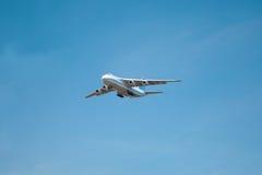 Un volo bianco dell'aeroplano in un chiaro cielo blu-chiaro Immagine Stock