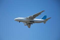 Un volo bianco dell'aeroplano in un chiaro cielo blu-chiaro Fotografie Stock Libere da Diritti