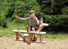 Un volo del ragazzo su un'oscillazione piana di legno in parco Fotografia Stock Libera da Diritti